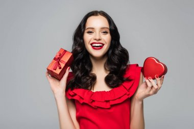 Cheerful woman with red lips holding heart-shaped gift box and wrapped present with bow isolated on grey stock vector