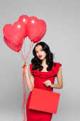 young woman holding red heart-shaped balloons and shopping bag isolated on grey