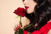 oříznutý pohled na brunetku mladá žena s červenými rty drží růže izolované na růžové