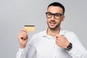 Lächelnder hispanischer Geschäftsmann, der mit dem Finger auf Kreditkarte zeigt