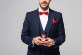 částečný pohled na usmívajícího se muže v elegantním obleku držícího šperkovnici se snubním prstenem izolovaným na šedi