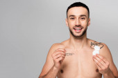 mladý hispánec bez košile drží zubní nit při pohledu na kameru izolované na šedé