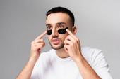junger hispanischer Mann trägt Augenklappen isoliert auf grau