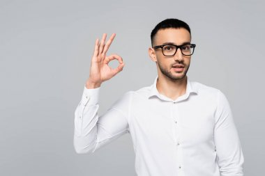 Young hispanic manager in eyeglasses showing ok gesture isolated on grey stock vector
