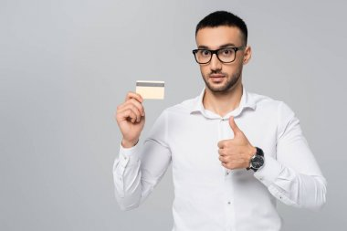 Young hispanic businessman showing thumb up while holding credit card isolated on grey stock vector