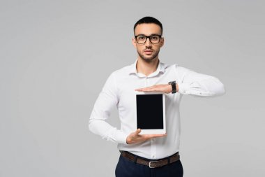 Brunette hispanic businessman in eyeglasses showing digital tablet with blank screen isolated on grey stock vector