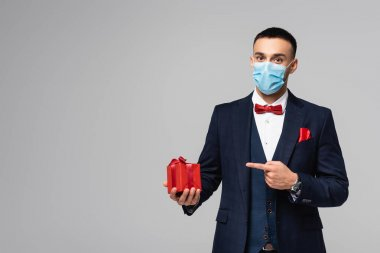 Young hispanic man in elegant suit and medical mask pointing at red gift box isolated on grey stock vector