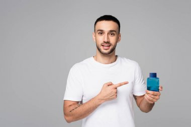 Young hispanic man in white t-shirt pointing at vial of eau de cologne isolated on grey stock vector