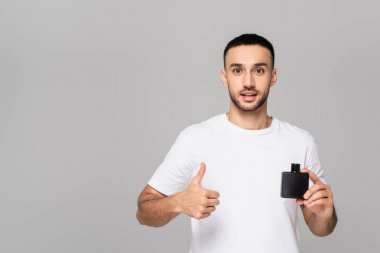 Positive hispanic man showing thumb up while holding eau de cologne isolated on grey stock vector