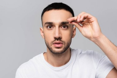 Brunette hispanic man looking at camera while tweezing eyebrows isolated on grey stock vector