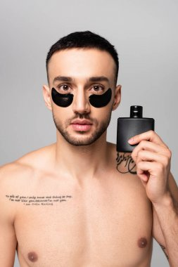 Shirtless hispanic man with eye patches holding vial of cologne water isolated on grey stock vector