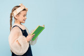 Photo little girl with pigtails smiling while reading book isolated on blue
