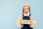 Photo smart kid in glasses smiling while holding books isolated on blue