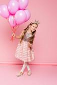 plná délka veselá holčička v šatech a koruně drží balónky na růžové
