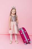 in voller Länge glückliches kleines Mädchen in Krone und Kleid, das neben Gepäck auf rosa steht