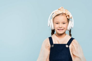 cheerful kid in headband with bow and wireless headphones listening music isolated on blue