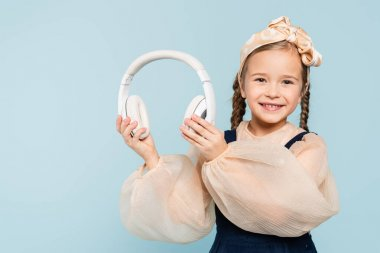 cheerful kid in headband with bow holding wireless headphones isolated on blue