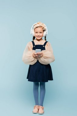 full length of cheerful kid in headband with bow and wireless headphones using smartphone isolated on blue