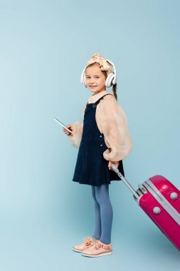 full length of happy little girl in wireless headphones using smartphone while standing with baggage on blue