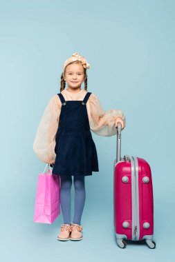 Full length of happy little girl holding shopping bag and standing with baggage on blue stock vector
