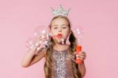 holčička v koruně foukání mýdlo bubliny na rozmazané popředí izolované na růžové