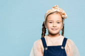 veselé dítě v čelence s lukem při pohledu na kameru izolované na modré