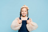 cheerful kid in headband with bow looking at camera and showing thumbs up isolated on blue