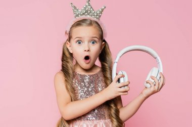 shocked little girl in crown holding wireless headphones isolated on pink