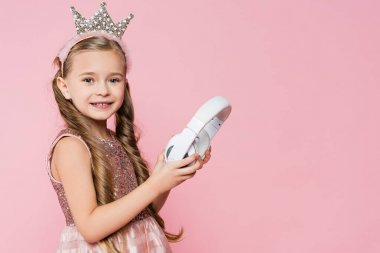 happy little girl in crown holding wireless headphones isolated on pink