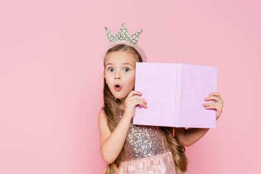 Surprised little girl in crown holding book isolated on pink stock vector