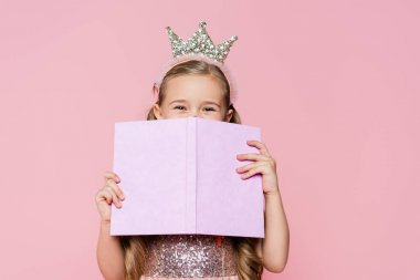 Little girl in crown covering face with book isolated on pink stock vector