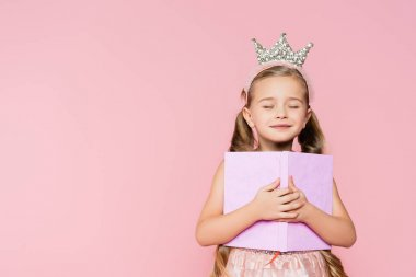 Smiling little girl with closed eyes in crown holding book isolated on pink stock vector