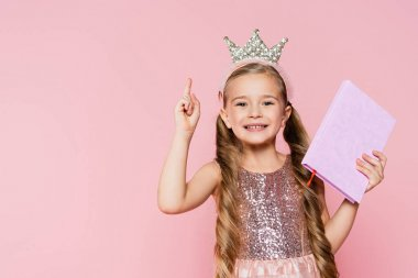 Smiling little girl in crown holding book and pointing with finger isolated on pink stock vector