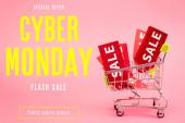 piros címkék eladó kis bevásárlókocsi közelében akciós ajánlat, cyber hétfő felirat rózsaszín