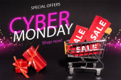 red gifts near toy cart with sale tags near special offers, cyber monday, shop now lettering on dark background, black friday concept