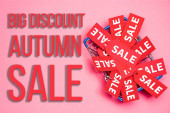 top view of sale tags in shopping basket near big discount autumn sale lettering on pink, black friday concept