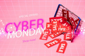 sale tags near shopping basket and special offers, cyber monday, shop now lettering on pink, black friday concept