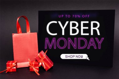 Red presents and shopping bag near placard with up to 70 percent off, cyber monday, shop now lettering on dark background stock vector