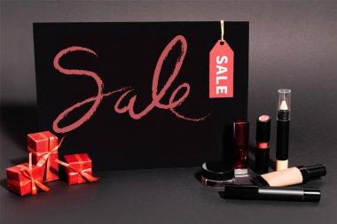Placard with sale lettering and gifts near decorative cosmetics on dark background stock vector