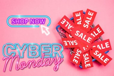 Top view of sale tags in shopping basket near shop now, cyber monday lettering on pink, black friday concept stock vector