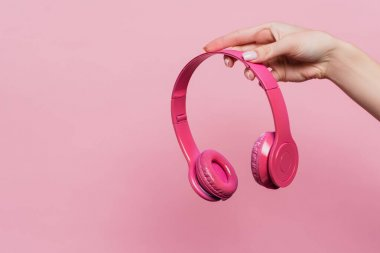 partial view of woman holding wireless headphones isolated on pink