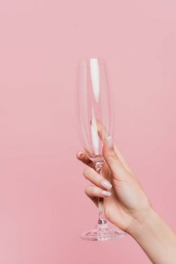 Partial view of woman holding empty champagne glass isolated on pink stock vector
