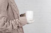 Oříznutý pohled na ženu v teplém svetru a rukavice drží šálek na bílém pozadí