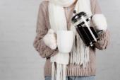 Vágott kilátás nő kötött pulóverben, sál és meleg kesztyű öntés kávé csésze fehér háttér