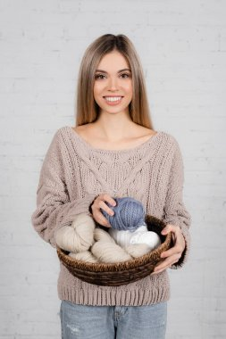 Cheerful woman in cozy sweater holding basket with woolen yarn on white background stock vector