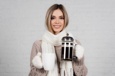Smiling woman in warm sweater, scarf and gloves holding cup and coffee pot on white background stock vector