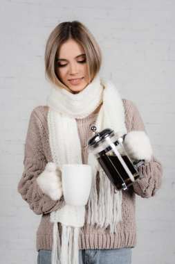 Smiling woman in warm sweater, gloves and scarf pouring coffee in cup on white background stock vector