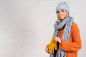 Cheerful woman in knitted wear holding gloves near white brick wall