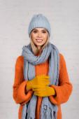 Junge Frau mit warmer Mütze, Strickpullover und Handschuhen blickt in die Kamera auf weißem Hintergrund