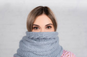 Young woman wrapped in knitted scarf looking at camera on grey background